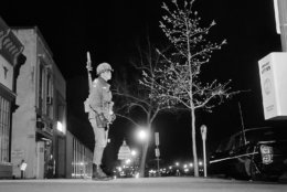 A soldier keeps watch as he stands guard along Pennsylvania Avenue near 7th Street, in the northwest section of Washington, April 6, 1968. The street is deserted, with a curfew imposed at 4 p.m., before darkness. The lighted dome of the U.S. capitol building is in the background. (AP Photo/Bob Schutz)