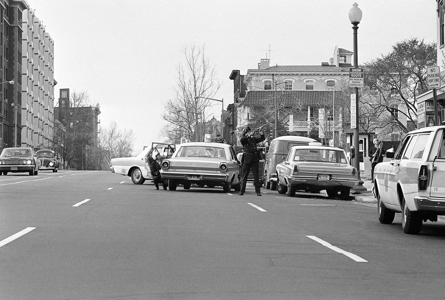 Police keep rifles at the ready as fellow law enforcement officers searched a house for an armed man at 11th and K Streets NW., April 7, 1968. Police were summoned after they received reported that a man, armed with a .22-caliber pistol, ran into the house. He was taken into custody without any shots being fired. (AP Photo/Charles Harrity)
