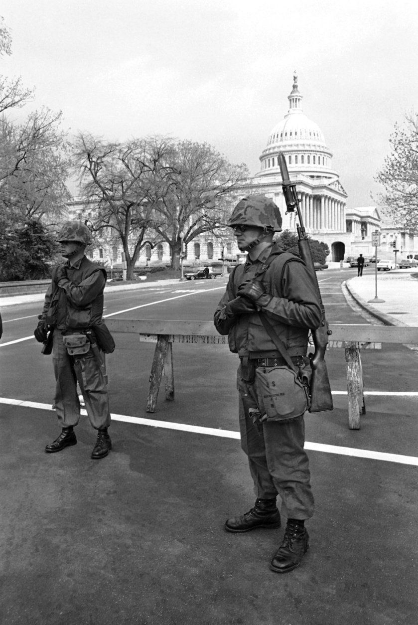 Two U.S. Marines stand guard at one of the entrances to the plaza at the U.S. Capitol Building in Washington on April 8, 1968. The city continued under rigid military control. (AP Photo/Charles Gorry)