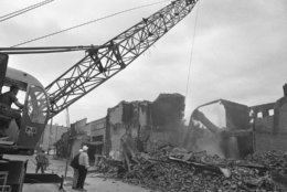 A demolition crew, using a crane with a weighted ball, goes about the task of leveling the walls of fire gutted buildings on 7th Street near Florida Avenue in the northwest section of Washington, D.C., on April 8, 1968 as the cleanup of damaged areas begins. (AP Photo/Henry Burroughs)