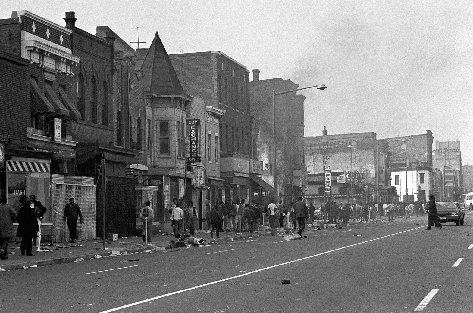 People mill around debris-covered sidewalks on Seventh Street, N.W. near U Street in Washington on April 5, 1968, in a predominantly African American business district. Smoke still rises from building in canter. (AP Photo/Bob Schutz)