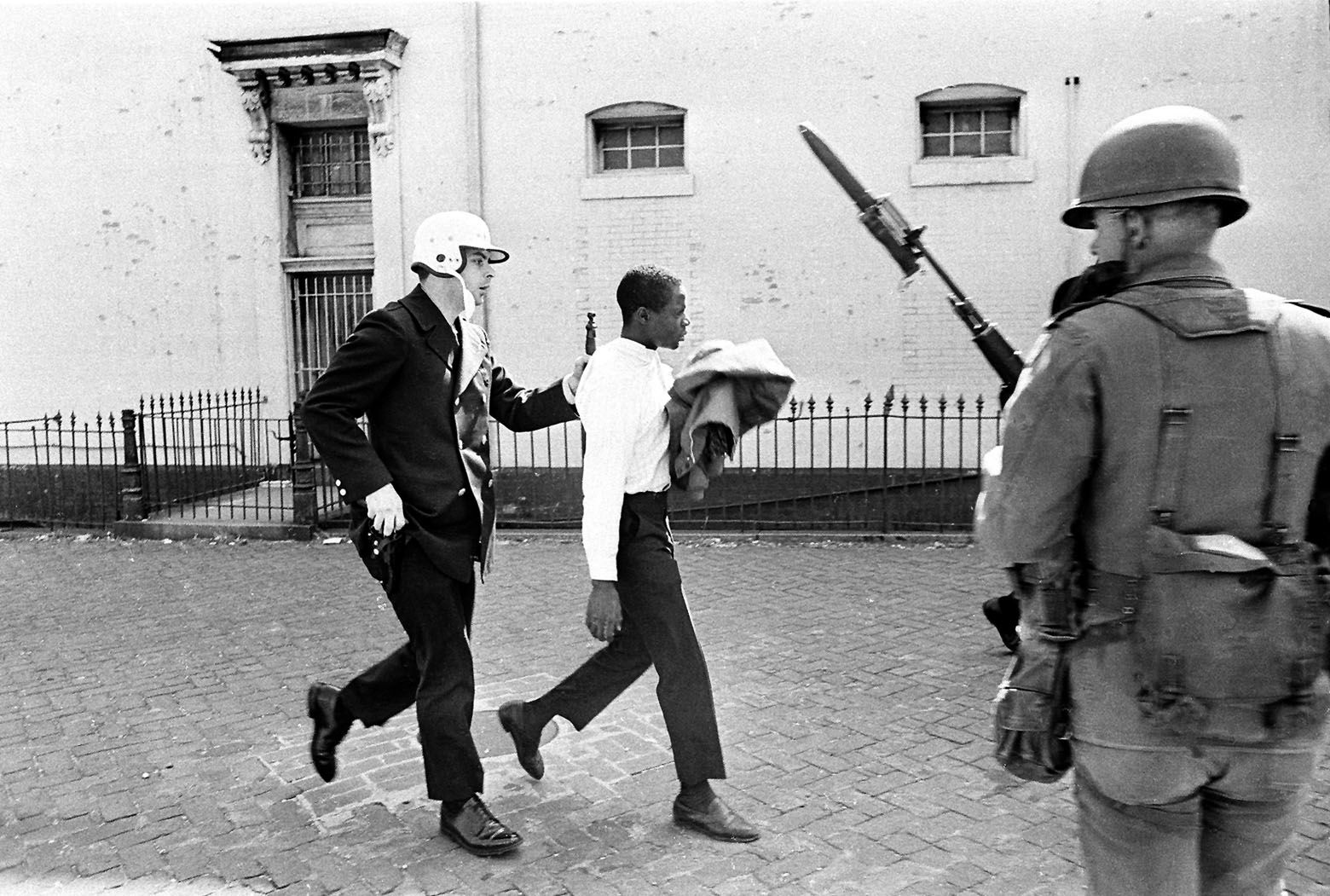 A Washington policeman, his hand near his gun, leads away a looter after arresting him near 7th and K Sts. in northwest Washington, D.C. on April 6, 1968. A U.S. Army trooper stands at right. Rioting broke out after the assassination of civil rights leader Dr. Martin Luther King, Jr., in Memphis, Tenn. on April 4. (AP Photo)