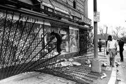 A policeman climbs over a protective screen and through the shattered glass front of a liquor store on 14th Street in Washington D.C. on April 5, 1968.  Violence broke out the day before in response to the assasination of the Rev. Martin Luther King Jr.  (AP Photo)