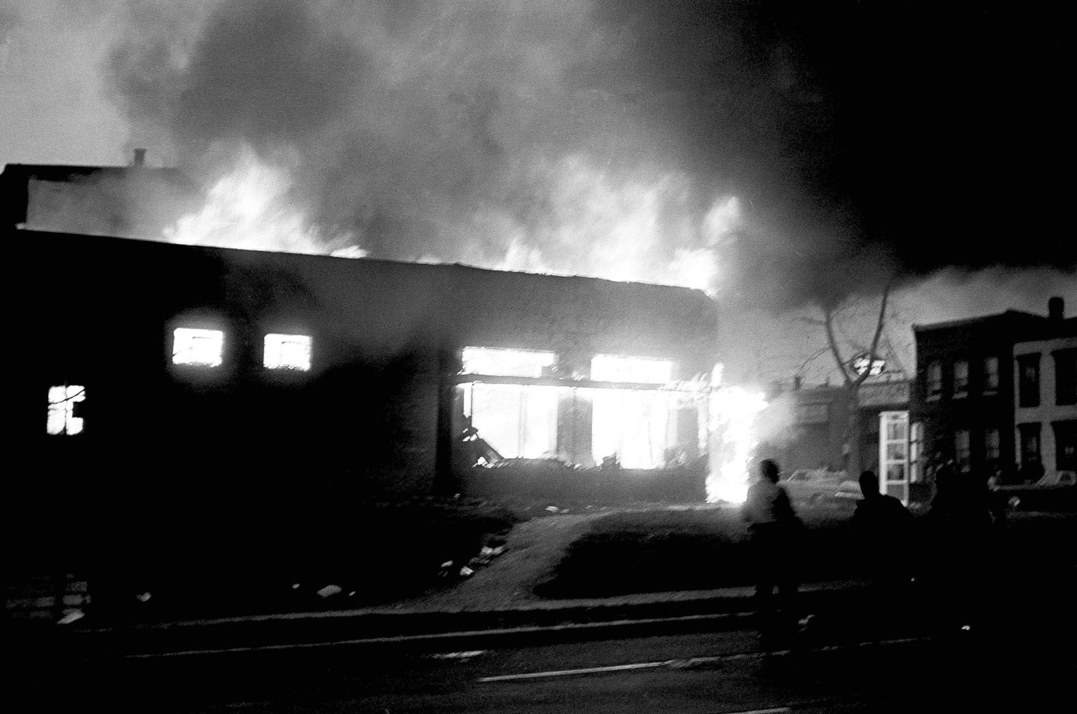 Men in foreground dash past a burning building in northeast Washington at the Third and K Streets on April 5, 1968, in wake of looting and burning, an aftermath of the assassination of Dr. Martin Luther King Jr. in Memphis, Tennessee on April 4. (AP Photo/Dozier Mobley)