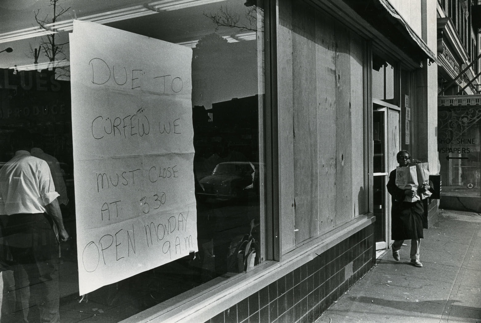 "The unrest prompted a strict curfew for several days. This store carries a sign reading: ""Due to curfew we must cose at 3:30. Open Monday 9 a.m."" Reprinted with permission of the DC Public Library, Star Collection, © Washington Post."