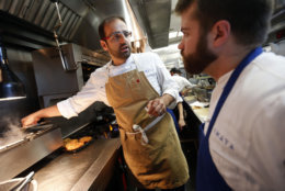 In this May 31, 2016 photo, Chef Alon Shaya, left, proprietor of Shaya Restaurant, works with sous chef Daniel Hollier at his restaurant in New Orleans. In 2015, Shaya opened his namesake restaurant, a bustling Israeli eatery on chic Magazine Street that the James Beard Foundation last month named the Best New Restaurant in the U.S. (AP Photo/Gerald Herbert)
