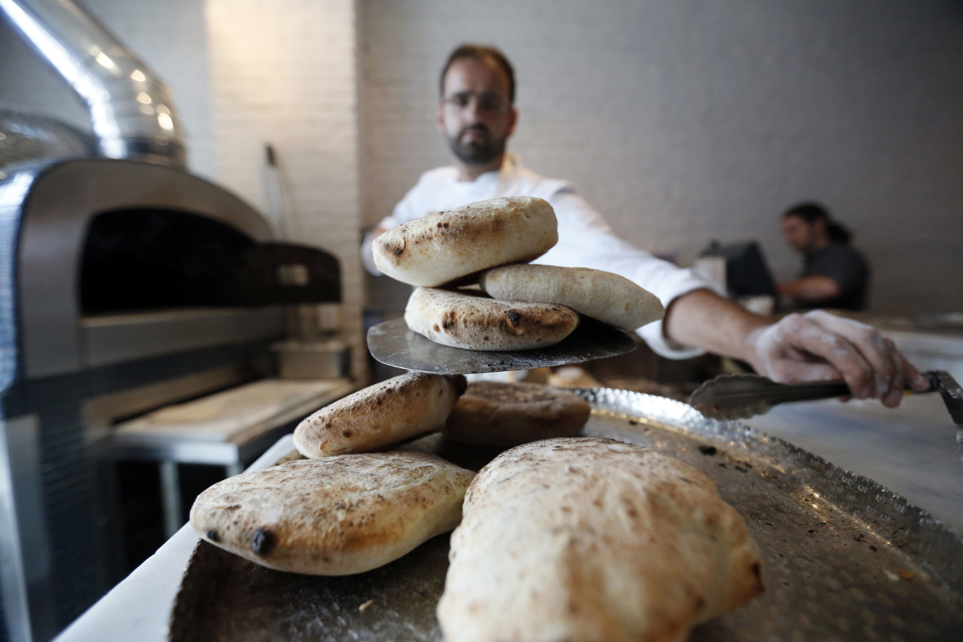 In this Tuesday, May 31, 2016 photo, Chef Alon Shaya, proprietor of Shaya Restaurant, makes house made pita at his wood fired oven at the restaurant in New Orleans. In 2015, Shaya opened his namesake restaurant, a bustling Israeli eatery on chic Magazine Street that the James Beard Foundation in May named the Best New Restaurant in the U.S. (AP Photo/Gerald Herbert)