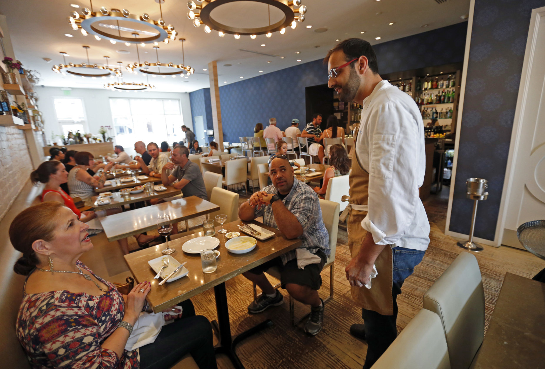 In this Tuesday, May 31, 2016 photo, Chef Alon Shaya, proprietor of Shaya Restaurant, talks to customers at his restaurant in New Orleans. In 2015, Shaya opened his namesake restaurant, a bustling Israeli eatery on chic Magazine Street that the James Beard Foundation in May named the Best New Restaurant in the U.S. (AP Photo/Gerald Herbert)