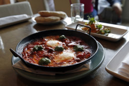 In this May 31, 2016 photo, Shakshouka, which is chermoula, Jerusalem artichokes, spicy chilies, tomato and egg, sits on a table at Shaya Restaurant, in New Orleans. In 2015, Shaya opened his namesake restaurant, a bustling Israeli eatery on chic Magazine Street that the James Beard Foundation in May named the Best New Restaurant in the U.S. (AP Photo/Gerald Herbert)
