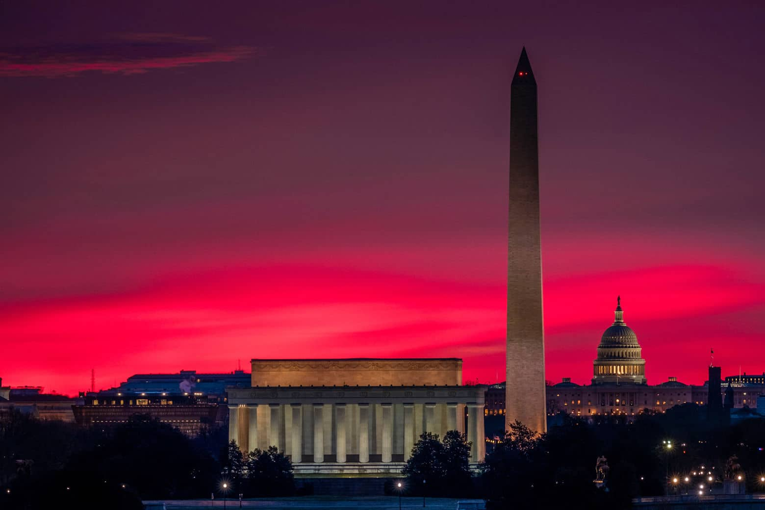 The sunrise behind the skyline of Washington turns the sky red on the first day of daylight saving time in 2017. (AP Photo/J. David Ake)