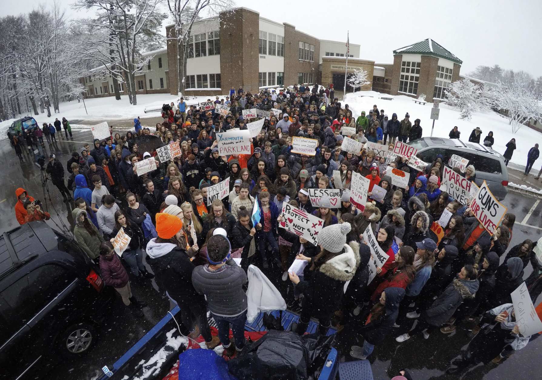 Students at Yarmouth High School participate in a walkout to protest gun violence, Wednesday, March 14, 2018, in Yarmouth, Maine. Leaders of the rally address the crowd from the back of a pick-up truck in front of the school. Yarmouth is one of the few schools in Maine that did not cancel school on Wednesday as the state digs out from the third major winter storm in two weeks. (AP Photo/Robert F. Bukaty)