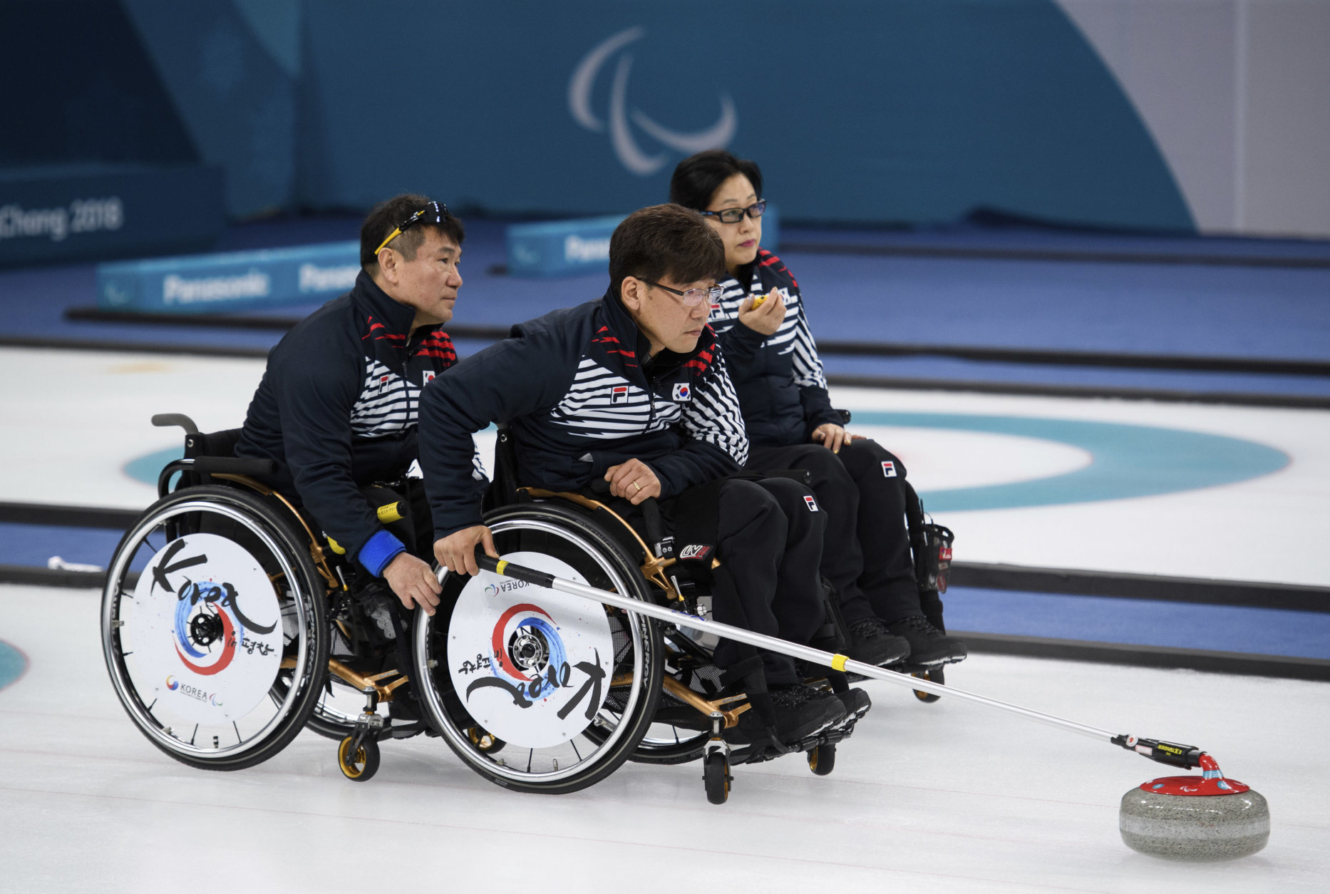 Soonseok Seo, center, of South Korea throws a stone during the Wheelchair Curling Bronze Medal Game between South Korea and Canada at the Gangneung Curling Centre  in Gangneung, South Korea at the 2018 Winter Paralympics Saturday, March 17, 2018. (Joel Marklund/OIS/IOC via AP)