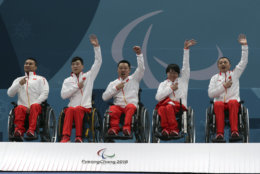Members of China's wheelchair curling team from left Wang Haitao, Chen Jianxin, Liu Wei, Wang Meng and Zhang Qiang point to their national flag on their jacket as they celebrate on the podium after defeating Norway in the Wheelchair Curling gold medal match for the 2018 Winter Paralympics at the Gangneung Curling Centre in Gangneung, South Korea, Saturday, March 17, 2018.(AP Photo/Ng Han Guan)