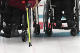 China's Wang Haitao throws a stone as teammate Liu Wei holds his Wheelchair steady during a Wheelchair Curling gold medal match against Norway for the 2018 Winter Paralympics at the Gangneung Curling Centre in Gangneung, South Korea, Saturday, March 17, 2018.(AP Photo/Ng Han Guan)