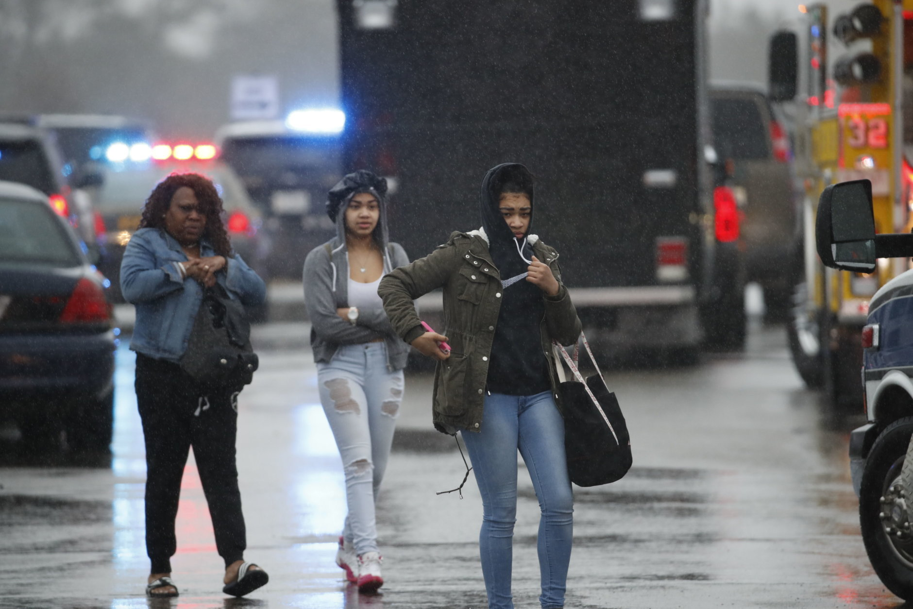 Two students and a mother leave Great Mills High School, the scene of a shooting, Tuesday morning, March 20, 2018 in Great Mills, Md. The shooting left at least three people injured including the shooter. (AP Photo/Alex Brandon  )