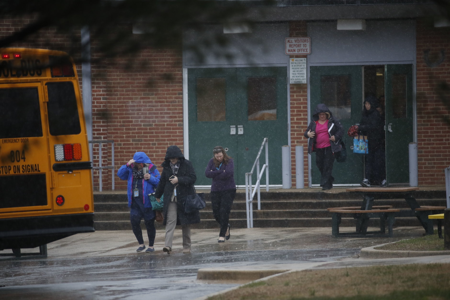 Teachers and school employees depart Great Mills High School, the scene of a shooting, Tuesday, March 20, 2018 in Great Mills, Md.  A teenager wounded a girl and a boy inside his Maryland high school Tuesday before an armed school resource officer was able to intervene, and each of them fired one more round as the shooter was fatally wounded, a sheriff said.  St. Mary's County Sheriff Tim Cameron said the student with the handgun was declared dead at a hospital, and the other two students were in critical condition. He said the officer was not harmed.  (AP Photo/Alex Brandon)