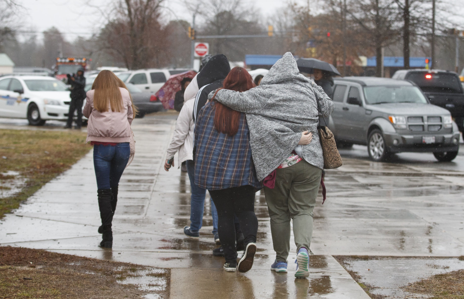 Parents walks their children, students from Great Mills High School, after picking them up from Leonardtown High School in Leonardtown, Md., Tuesday, March 20, 2018.   A teenager wounded a girl and a boy inside his Maryland high school Tuesday before a school resource officer was able to intervene, and each of them fired one more round as the shooter was fatally wounded, a sheriff said. St. Mary's County Sheriff Tim Cameron said the student with the handgun was declared dead at a hospital, and the other two students were in critical condition. (AP Photo/Carolyn Kaster)