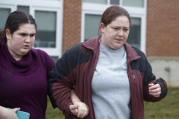 A mother walks her daughter, a student from Great Mills High School, to the car as she picks her up from Leonardtown High School in Leonardtown, Md., Tuesday, March 20, 2018.  A teenager wounded a girl and a boy inside his Maryland high school Tuesday before a school resource officer was able to intervene, and each of them fired one more round as the shooter was fatally wounded, a sheriff said. St. Mary's County Sheriff Tim Cameron said the student with the handgun was declared dead at a hospital, and the other two students were in critical condition.  (AP Photo/Carolyn Kaster)