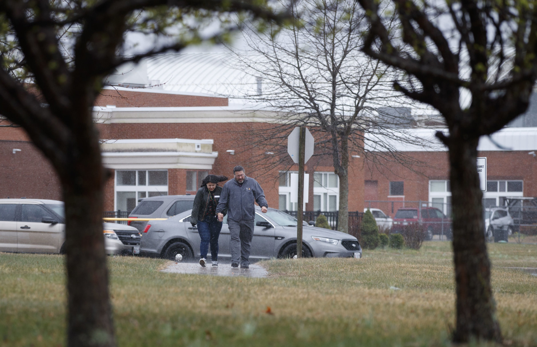 Parents walk with their children, students from Great Mills High School, as they pick them up from Leonardtown High School in Leonardtown, Md., Tuesday, March 20, 2018.   A teenager wounded a girl and a boy inside his Maryland high school Tuesday before a school resource officer was able to intervene, and each of them fired one more round as the shooter was fatally wounded, a sheriff said. St. Mary's County Sheriff Tim Cameron said the student with the handgun was declared dead at a hospital, and the other two students were in critical condition. (AP Photo/Carolyn Kaster)