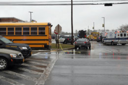 Vehicles of first responders and school buses are parked at the entrance to Great Mills High School Tuesday, March 20, 2018, in Great Mills. A student with a handgun shot two classmates inside the high school before he was fatally wounded during a confrontation with a school resource officer, a sheriff said. (AP Photo/Alex Brandon)