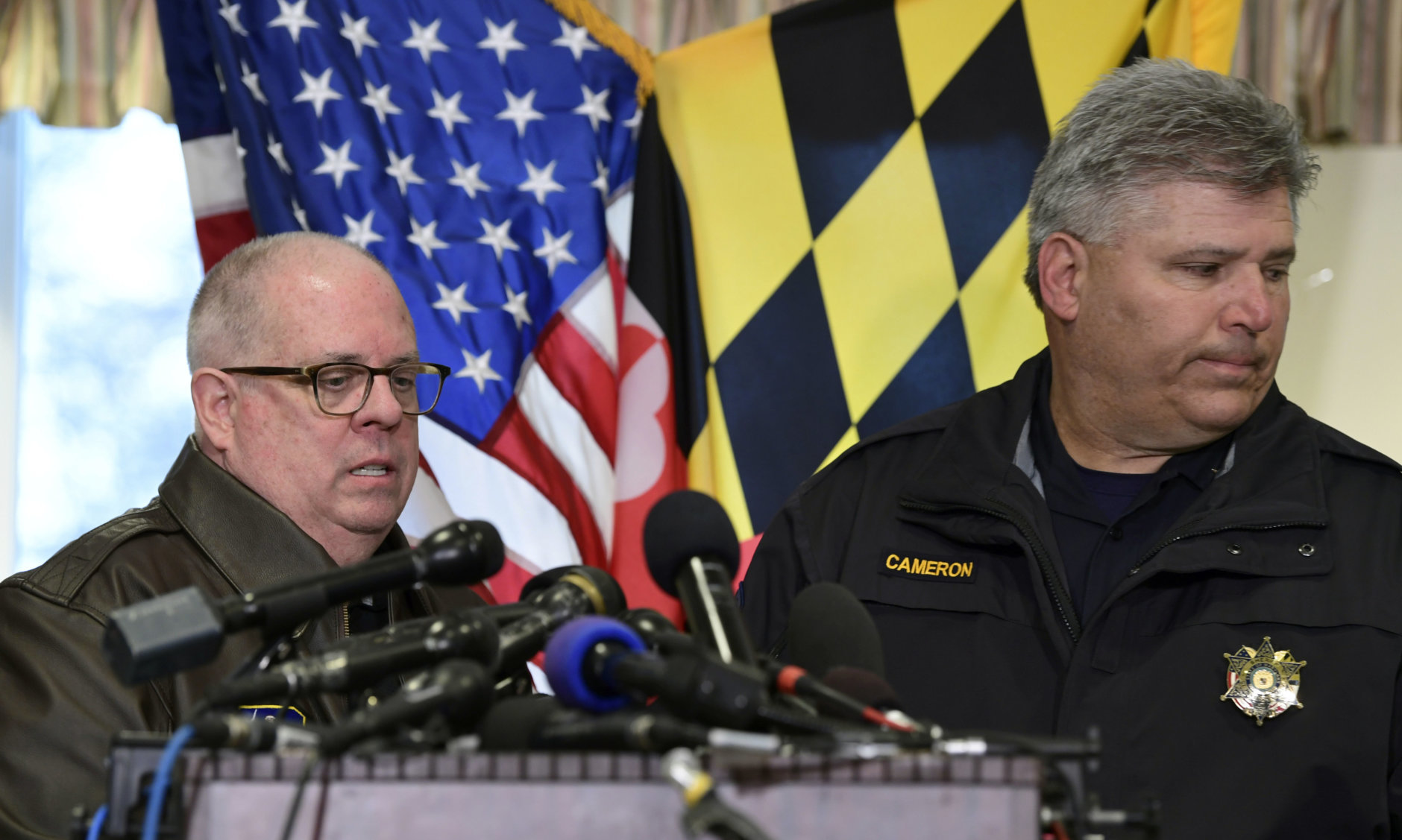 St. Mary's County Sheriff Tim Cameron, right, steps aside as Maryland Gov. Larry Hogan, left, begins to speak about the shooting at Great Mills High School during a news conference in Great Mills, Md., Tuesday, March 20, 2018. (AP Photo/Susan Walsh)