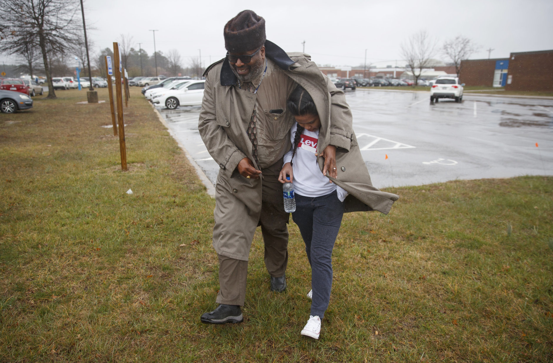 A father shelters his daughter, a student from Great Mills High School, from the rain as they picks her up from Leonardtown High School in Leonardtown, Md., Tuesday, March 20, 2018.  A student with a handgun shot two classmates inside his Maryland high school before he was fatally wounded during a confrontation with a school resource officer, a sheriff said. (AP Photo/Carolyn Kaster)