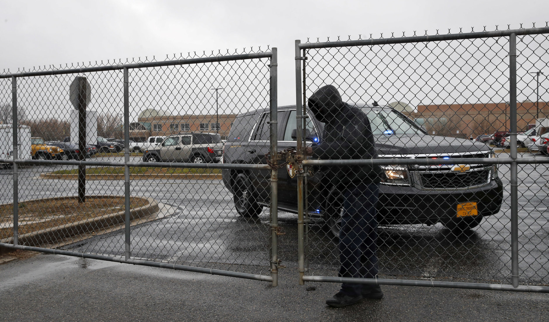 A man checks a locked gate to the parking lot of Great Mills High School, the scene of a shooting, Tuesday, March 20, 2018, in Great Mills. A student with a handgun shot two classmates inside the school before he was fatally wounded during a confrontation with a school resource officer, a sheriff said.  (AP Photo/Alex Brandon)