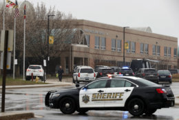 A law enforcement officer walks in front of Great Mills High School, the scene of a shooting, Tuesday, March 20, 2018, in Great Mills. A student with a handgun shot two classmates inside the school before he was fatally wounded during a confrontation with a school resource officer, a sheriff said.  (AP Photo/Alex Brandon)
