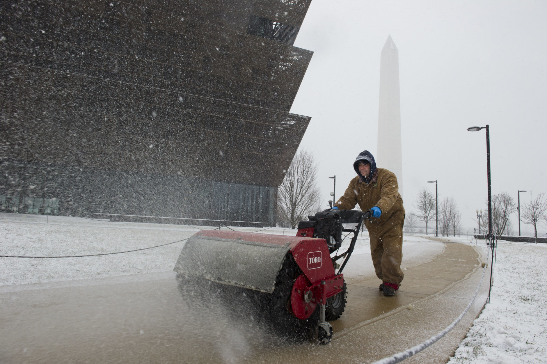 The Washington Monument is seen in the background as a worker clears snow from a sidewalk at the National Museum of African American History and Culture during a Spring snowstorm in Washington, Wednesday, March 21, 2018. (AP Photo/Cliff Owen)