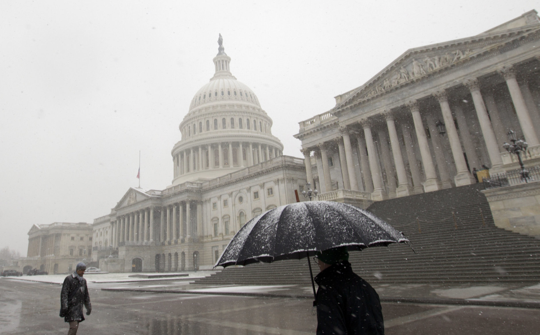 Pedestrians walk under a snow fall outside of U.S. Capitol building, Wednesday, March 21, 2018, in Washington.The storm shut down federal offices in the D.C. area, closed schools and stopped two major commuter rail systems from operating. (AP Photo/Jose Luis Magana)