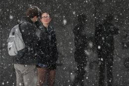 Washington visitor Haley Rich and Eric Merritt from Las Vegas, Nev., pause at the Vietnam Veterans Memorial on the National Mall in Washington during a Spring snow storm, Wednesday, March 21, 2018. The coming spring nor'easter caused the federal government to close its offices in the Washington area. (AP Photo/Manuel Balce Ceneta)