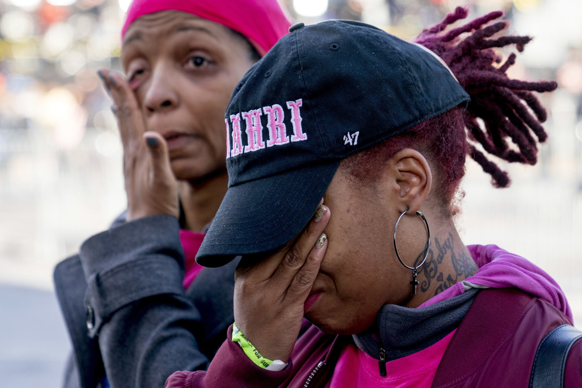 """Nicole Spriggs, left, and April Amarsh, right, cry as they arrive at the """"March for Our Lives"""" rally in support of gun control in Washington, Saturday, March 24, 2018. They were among friends and family attending in memory of college bound Jamahri Sydnor, 17, who was shot to death in August 2017, in Washington. (AP Photo/Andrew Harnik)"""