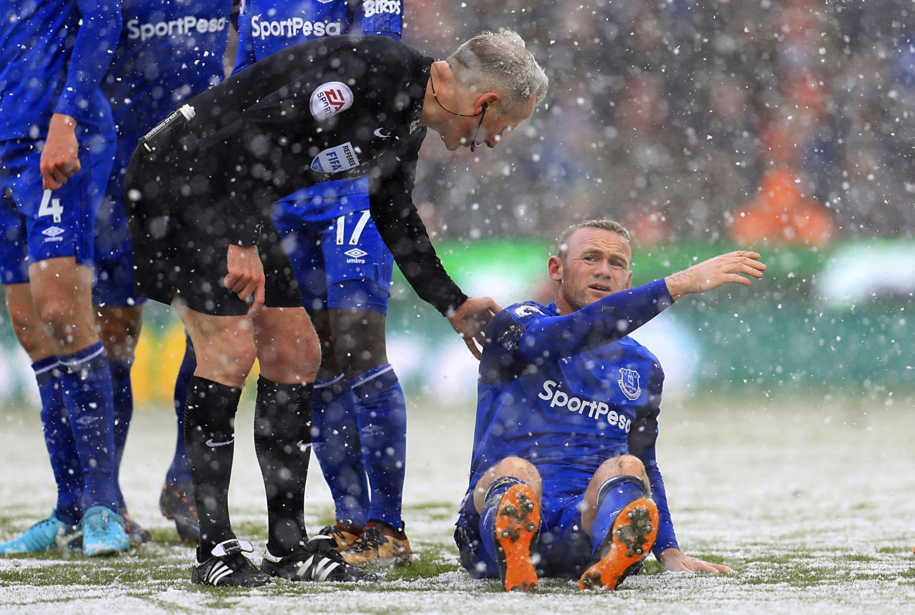 Everton's Wayne Rooney is helped up by referee Martin Atkinson during the English Premier League soccer match between Stoke City and Everton, at the bet365 Stadium, in Stoke, England, Saturday March 17, 2018. (Mike Egerton/PA via AP)
