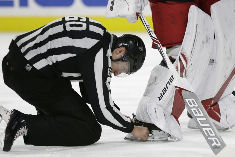 c0d523095 An official removes the puck lodged in Carolina Hurricanes goalie Cam Ward s  skate during the first period of the team s NHL hockey game against.