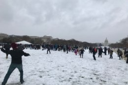 A snowball fight takes place at the National Mall during a spring snow storm on Wednesday, March 21, 2018. (WTOP/Dick Uliano)