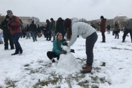 Two people make a snowman with the the thin layer of snow that fell on the National Mall on Wednesday, March 21, 2018. (WTOP/Dick Uliano)