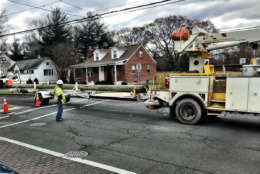 Crews arrive with replacement poles after the wind knocked down the poles in Leesburg, Virginia. (WTOP/Neal Augenstein)