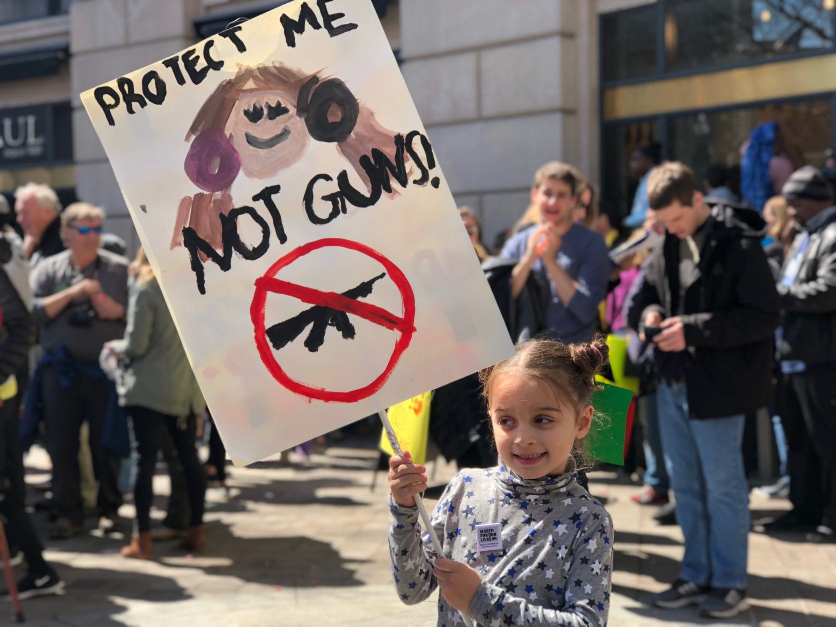 """At D.C.'s March For Our Lives event on Saturday, March 24, 6-year-old Florence Morton from New York City holds up a sign that reads, """"Protect Me Not Guns."""" (WTOP/Kate Ryan"""