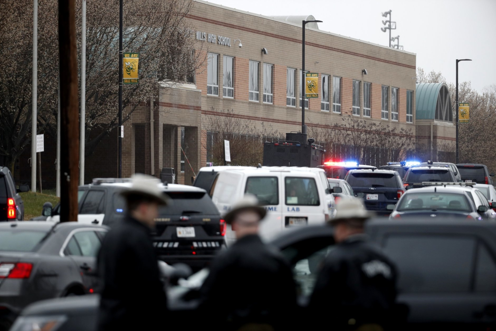 """Deputies and federal agents converge on Great Mills High School, the scene of a shooting, Tuesday morning, March 20, 2018 in Great Mills, Md. The shooting left at least three people injured including the shooter. Authorities said the situation is """"contained."""" (AP Photo/Alex Brandon  )"""