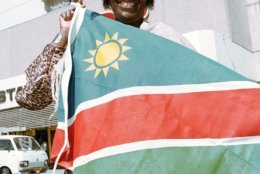 A Hararo woman holds the new Namibian flag which is to be hoisted in a ceremony when Nambia becomes independent after being under South African rule for 75 years, in Windhoek, Namibia, March 19, 1990. (AP Photo/John Parkin)