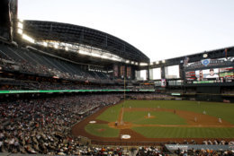 When Chase Field opened in 1998, it was the first stadium in the United States with a retractable roof over a natural-grass field. Twenty years after its opening, it's one of the cheaper stadiums to visit coming it No. 26 with an average cost of $56. File. (AP Photo/Ross D. Franklin)