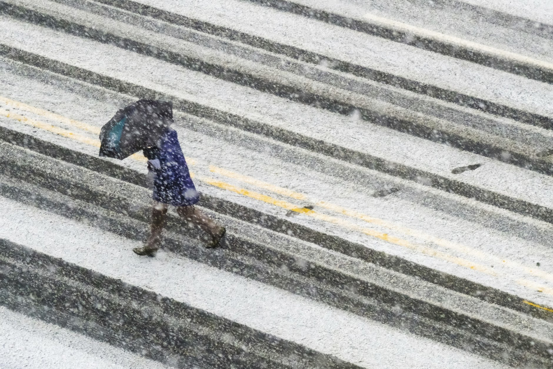 A pedestrian races across the snow covered and tire streaked street in Washington during a spring storm, Wednesday, March 21, 2018. (AP Photo/J. David Ake)