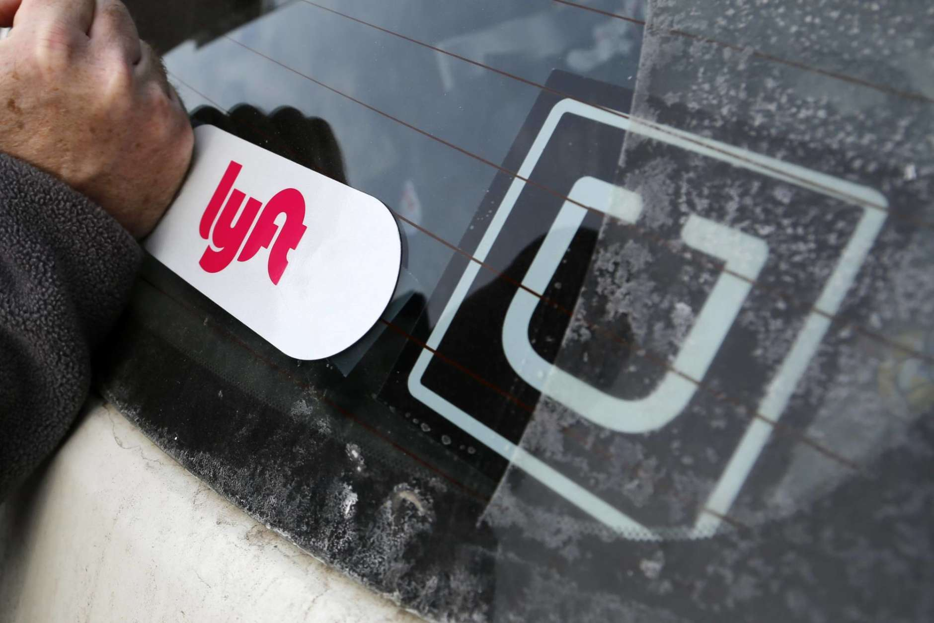 FILE- In this Jan. 31, 2018, file photo, a Lyft logo is installed on a Lyft driver's car next to an Uber sticker in Pittsburgh. Lyft and Uber are expanding deeper into health care by offering to take more patients to and from non-emergency medical appointments in markets around the country. (AP Photo/Gene J. Puskar, File)