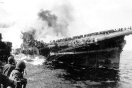 In this image provided by the U.S. Navy, the USS Santa Fe lies alongside the heavily listing USS Franklin to provide assistance after the aircraft carrier had been hit and set afire by a single Japanese dive bomber, during the Okinawa invasion, on March 19, 1945, off the coast of Honshu, Japan.  (AP Photo/U.S. Navy)