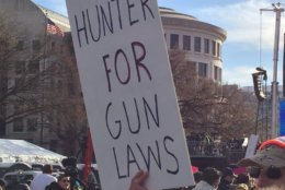 "In this photo, Eric Ripper, of Fort Belvoir, Virginia, holds a sign that says, ""Hunter for gun laws."" (WTOP/John Domen)"