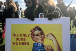 "A woman holds up a sign of Rosie the Riveter that says, ""The only guns we need."" (WTOP/Melissa Howell)"