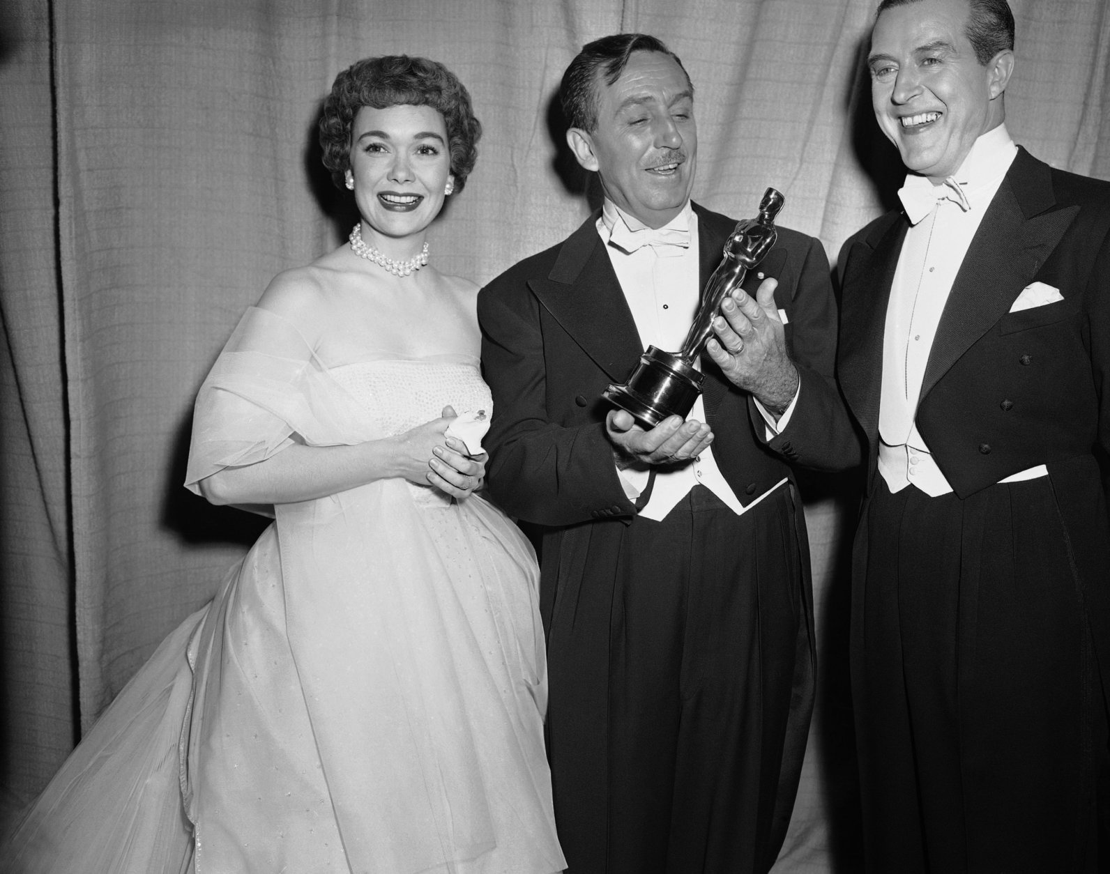 """Walt Disney (center) receives Academy Award for best two-reel short subjects, """"Water Birds"""" from Jane Wyman and Ray Milland, right, at the 1953 Academy Awards presentation in Hollywood on March 19, 1953. (AP Photo)"""