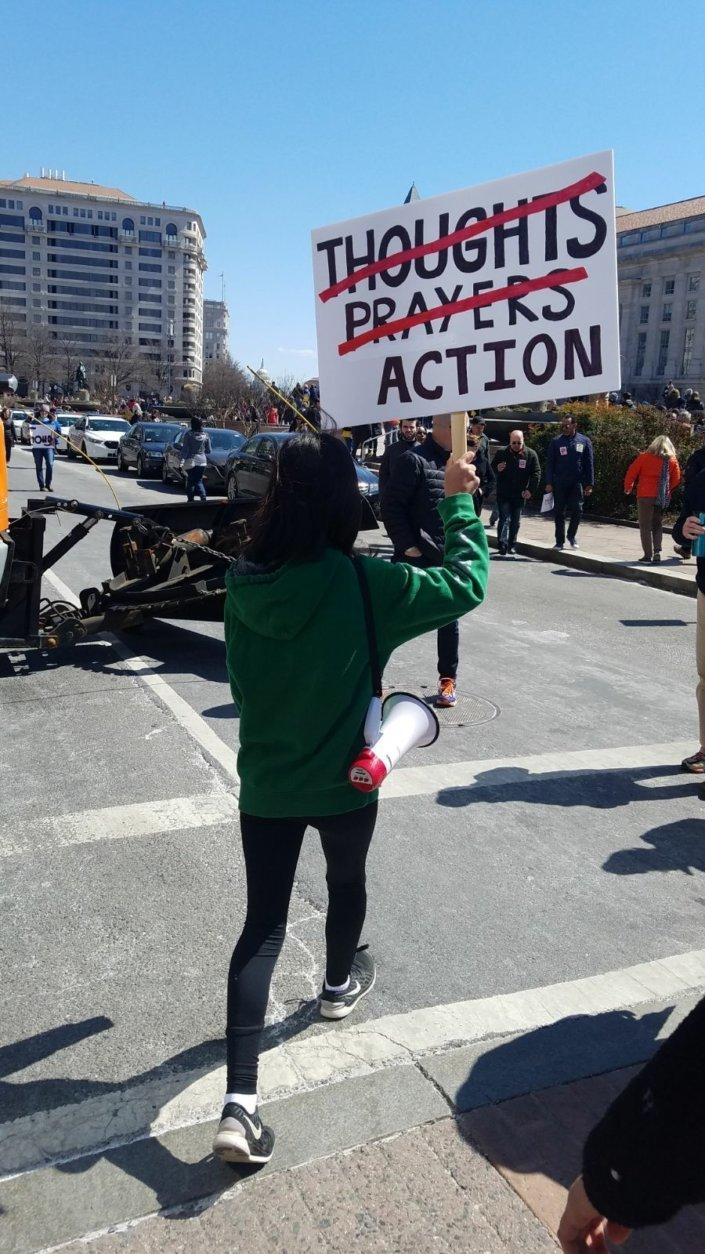 A marcher in D.C. with a sign that demands action. (Courtesy Olivia Prieto)