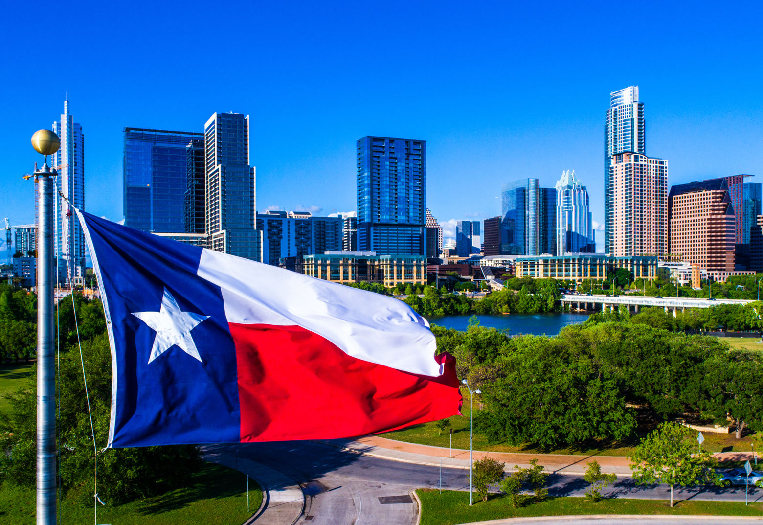 Aerial drone view Austin Texas Perfect Texas flag flying in front of Austin Texas downtown skyline cityscape sunny perfect day
