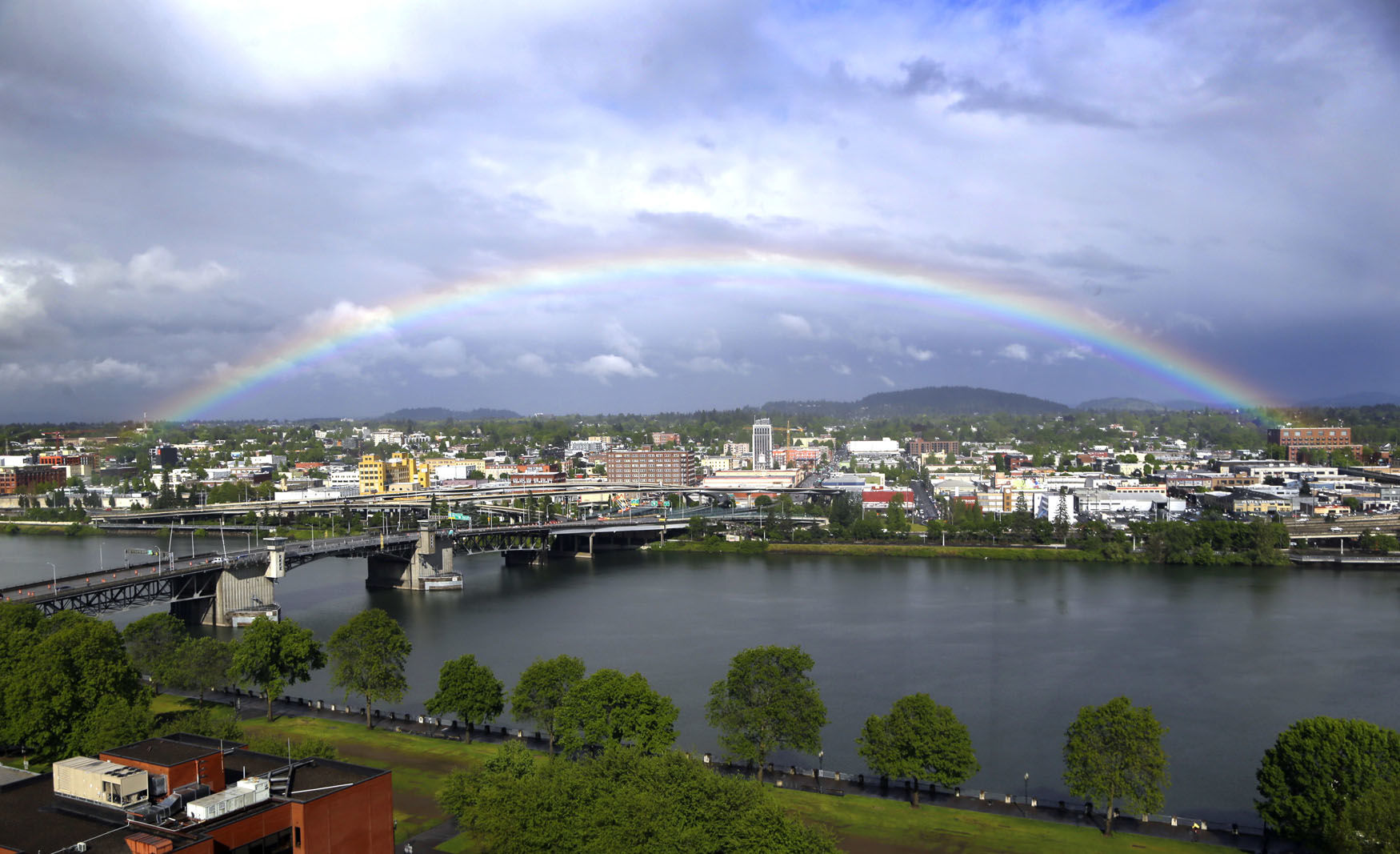 A rainbow pops out under dark rain clouds over the Willamette River in downtown Portland, Ore., Thursday, May 11, 2017. (AP Photo/Don Ryan)